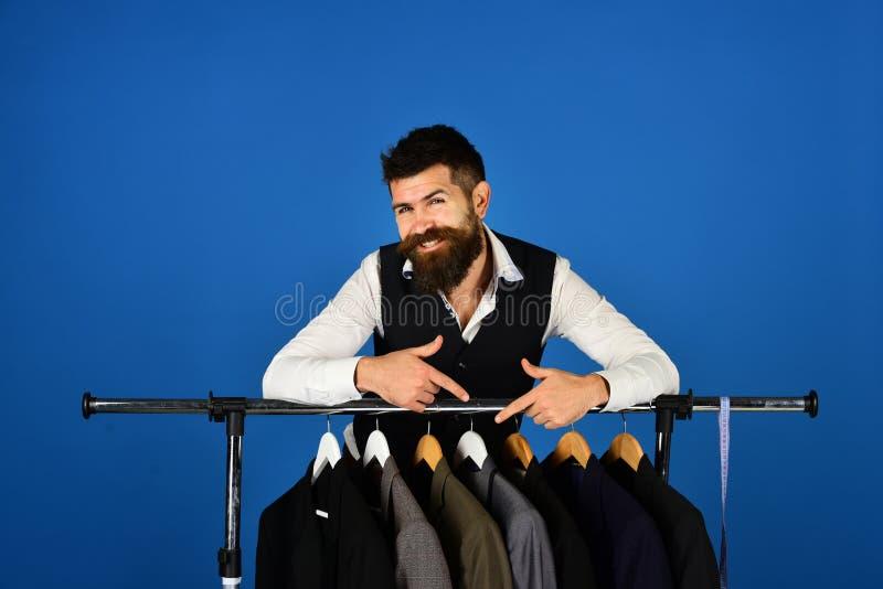 El ayudante o el vendedor de tienda se inclina en suspensiones de ropa con los trajes imagen de archivo libre de regalías