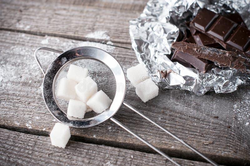El azúcar de terrón en un tamiz y un chocolate oscuro negro del metal junta las piezas de o fotografía de archivo