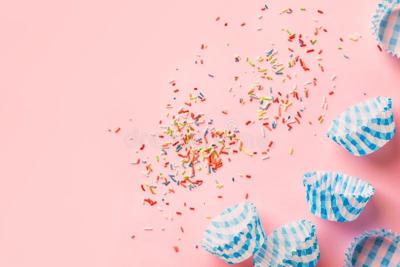 El azúcar multicolor del arco iris asperja las tazas de papel azules de la magdalena en fondo rosado en colores pastel Hornada de foto de archivo