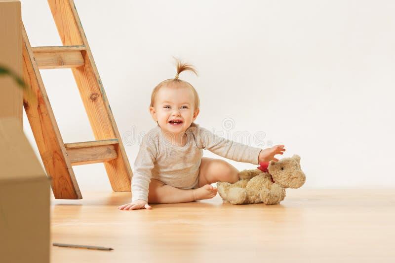 El azul amistoso observó al bebé que se sentaba en el piso dentro fotos de archivo