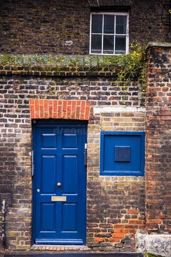 El azul brillante coloreó la puerta inglesa tradicional de la casa en Londres imagen de archivo libre de regalías