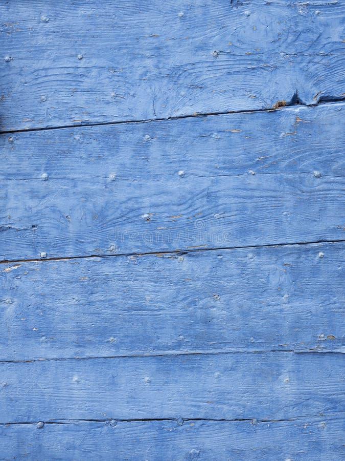 El azul brillante pintó tablones de madera viejos con las grietas y los clavos imagen de archivo libre de regalías