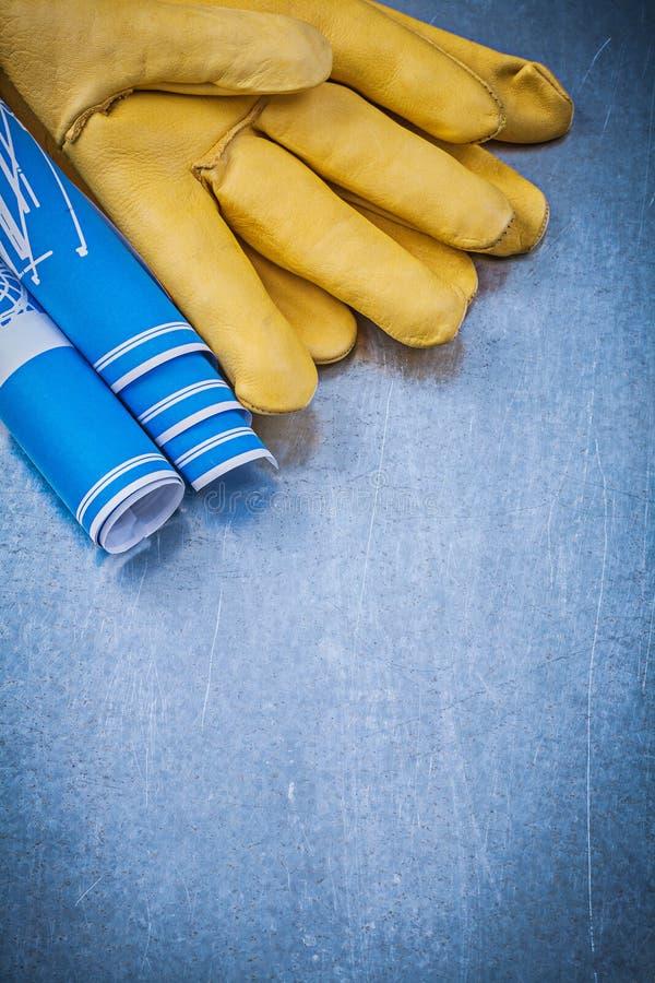 El azul de cuero de los guantes protectores rodó planes de la construcción en meta imagenes de archivo