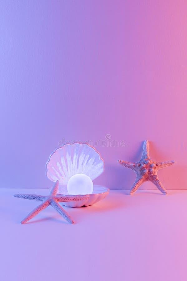 El azul de neón en colores pastel y la pintura ligera rosada en concha marina y la perla adornan con los pescados de la estrella fotografía de archivo