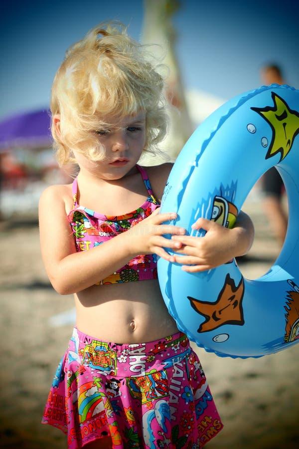El azul observó a la niña rubia en la playa en el verano fotografía de archivo