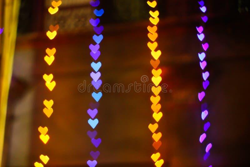 El azul púrpura del amarillo en forma de corazón del bokeh coloreó listo para su capa del diseño fotos de archivo libres de regalías