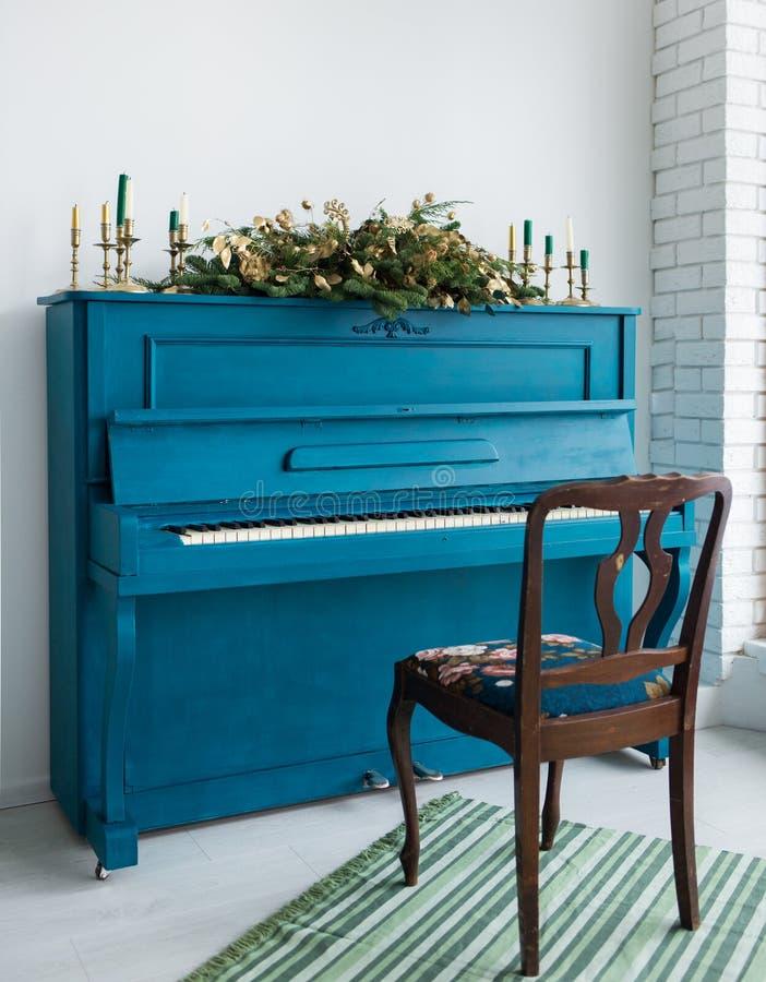 El azul pintó el piano viejo adornado con la guirnalda larga de la Navidad imagenes de archivo