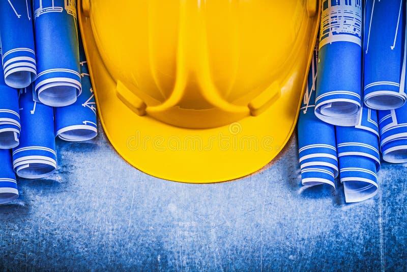 El azul rodó el casco amarillo del edificio de los dibujos de ingeniería en el metal fotografía de archivo