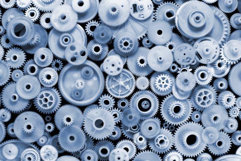 El azul teñió los engranajes y las ruedas dentadas plásticos en fondo negro imagen de archivo libre de regalías