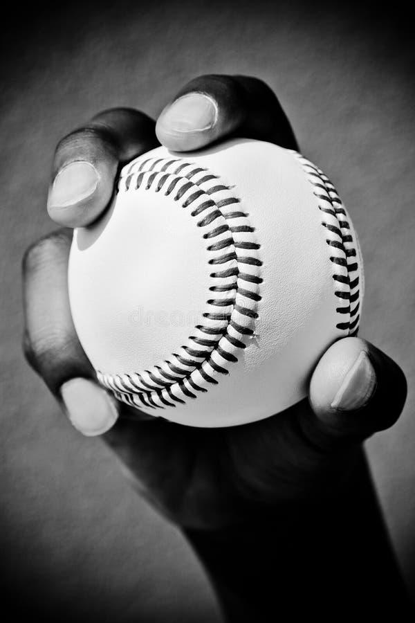 El béisbol en la mano derecha muestra costuras imágenes de archivo libres de regalías