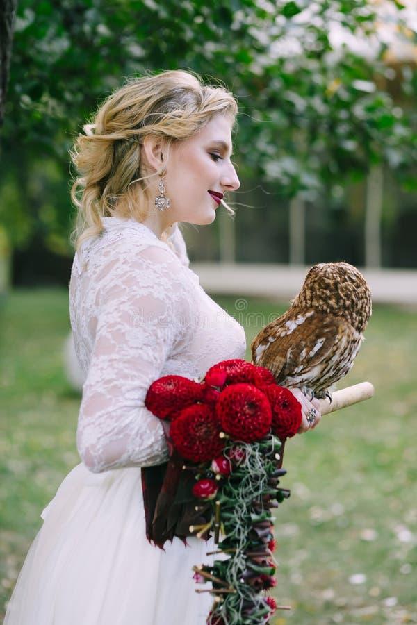 El búho se sienta en la mano del ` s de la muchacha La novia con el búho foto de archivo