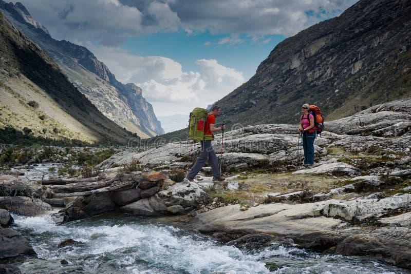 El backpacker del hombre y de la mujer en los Andes de Perú cruza una corriente salvaje de la montaña foto de archivo