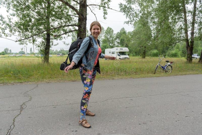 El backpacker feliz de la muchacha se coloca con una mochila en el camino, contra la perspectiva de árboles en un día de verano fotografía de archivo