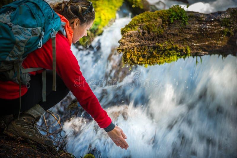 El Backpacker que lleva a cabo la mano debajo de la agua corriente del clearwater se cae imagen de archivo