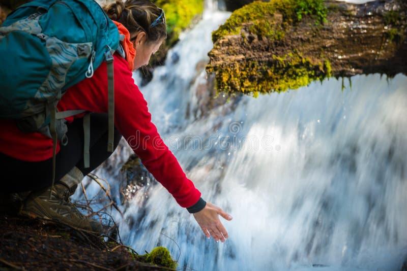 El Backpacker que lleva a cabo la mano debajo de la agua corriente del clearwater se cae imagen de archivo libre de regalías