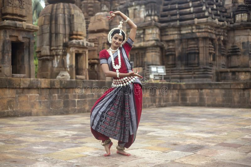 El bailarín clásico indio del odissi lleva el traje tradicional y la presentación delante del templo de Mukteshvara, Bhubaneswar, fotografía de archivo