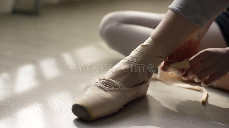 El bailarín de ballet implica sus pointes Bailarín de ballet que ata los zapatos de ballet antes de entrenar foto de archivo