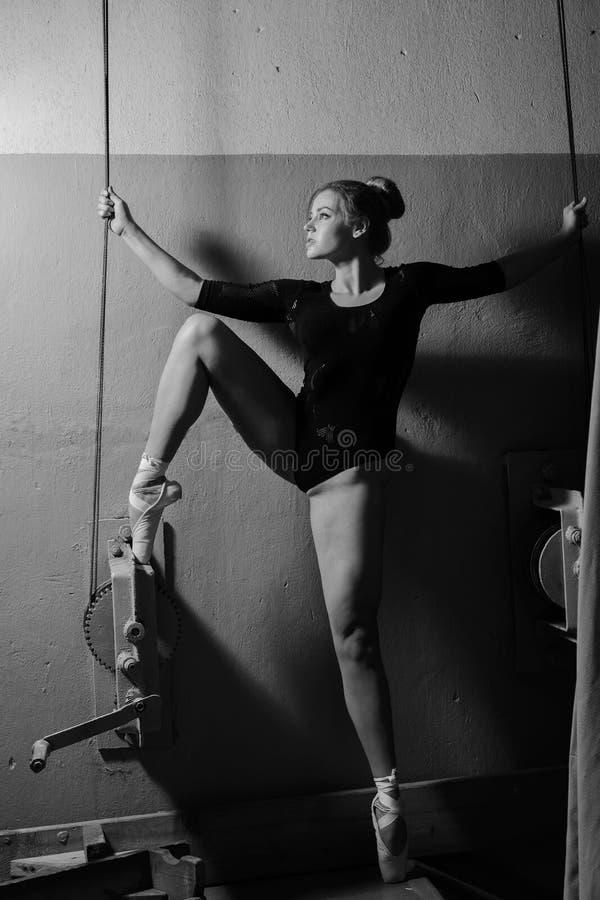 El bailarín de ballet joven en cuerpo negro se sostiene en la cuerda foto de archivo libre de regalías