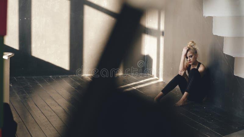El bailarín joven del adolescente está sufriendo después de que el bastidor de la pérdida se siente en piso en estudio de la danz fotos de archivo