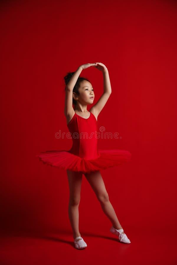 El bailarín lindo de la bailarina de la niña en vestido hermoso está bailando el salto en fondo rojo imagenes de archivo