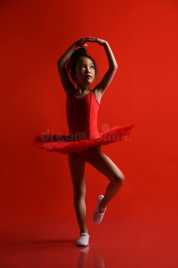 El bailarín lindo de la bailarina de la niña en vestido hermoso está bailando el salto en fondo rojo imagen de archivo
