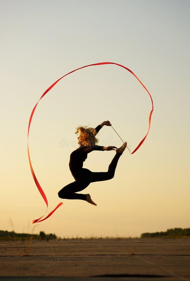 El bailarín que salta con la cinta fotografía de archivo