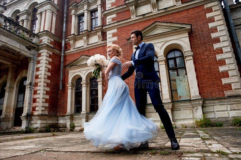 El baile de novia y del novio alrededor de las columnas del viejo estado Un novio alto, y una novia con el pelo rubio azul imágenes de archivo libres de regalías