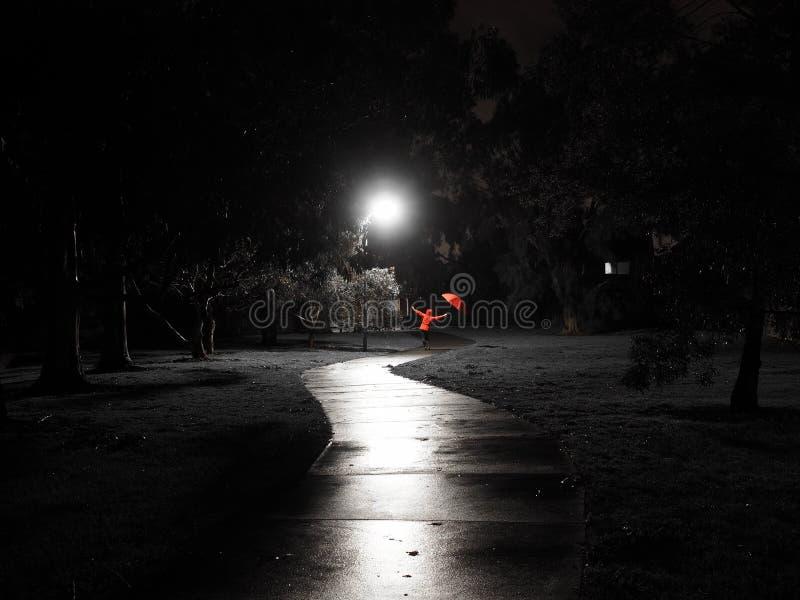 El baile femenino rojo con el paraguas rojo en una trayectoria oscura espeluznante de la bici se encendió por la luz de calle foto de archivo libre de regalías
