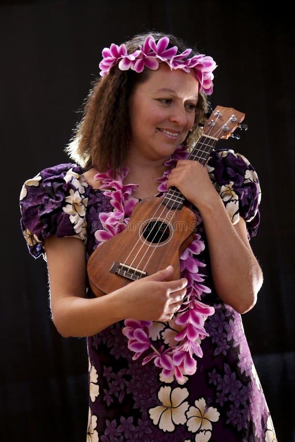 El baile hawaiano femenino sonriente de la muchacha y el canto con los instrumentos musicales les gusta el ukelele imagen de archivo
