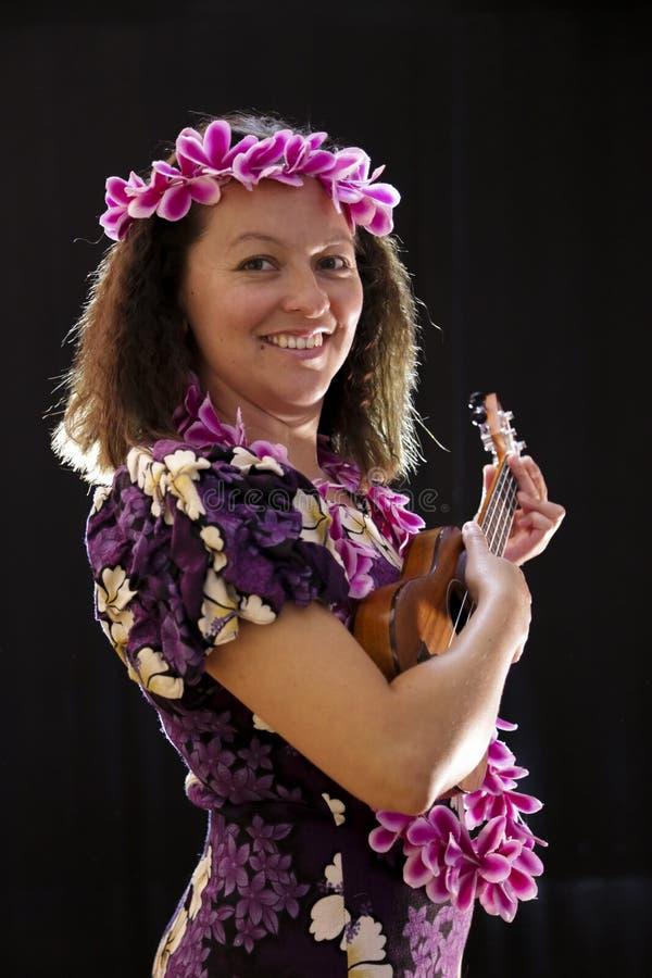 El baile hawaiano femenino sonriente de la muchacha y el canto con los instrumentos musicales les gusta el ukelele fotografía de archivo