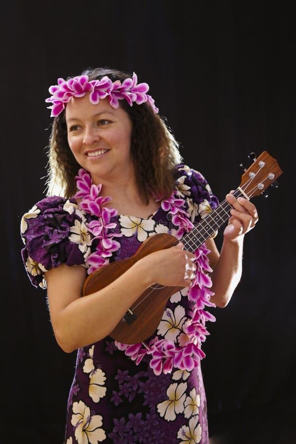 El baile hawaiano femenino sonriente de la muchacha y el canto con los instrumentos musicales les gusta el ukelele foto de archivo libre de regalías