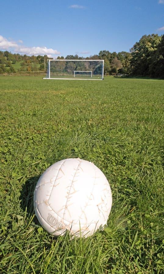 El balón de fútbol en el campo de hierba, meta fija el fondo imágenes de archivo libres de regalías
