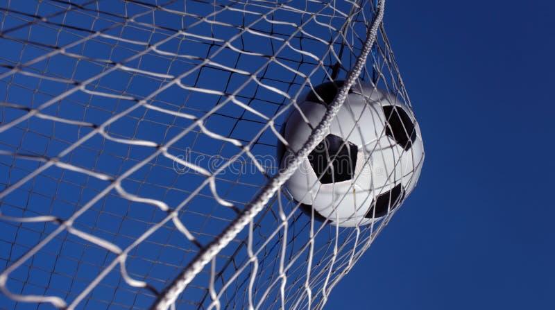 El balón de fútbol golpeó con el pie en una meta fotografía de archivo