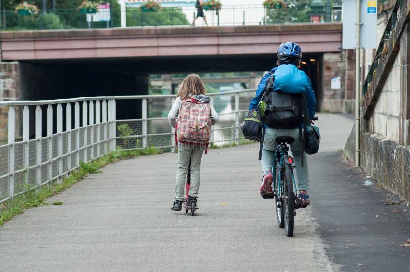 El balanceo de la mujer en bicicleta con el casco con la muchacha en vespa y la mochila en frontera riegan fotos de archivo libres de regalías