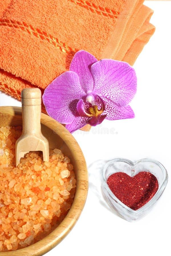El balneario fijó de la sal de baño anaranjada, de la toalla con la flor de la orquídea y del corazón rojo el día del ` s de la t fotografía de archivo libre de regalías