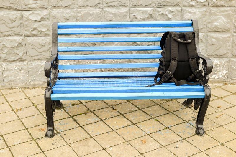 El banco azul en el parque en el pavimento tejado con una mochila negra ningún cuerpo imágenes de archivo libres de regalías