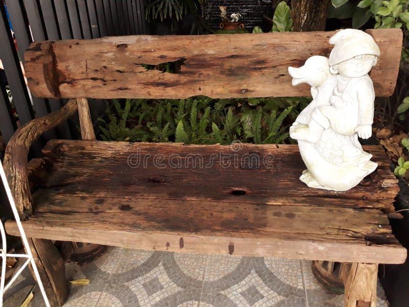 El banco de madera viejo allí es muñecas blancas del estuco colocadas fotos de archivo