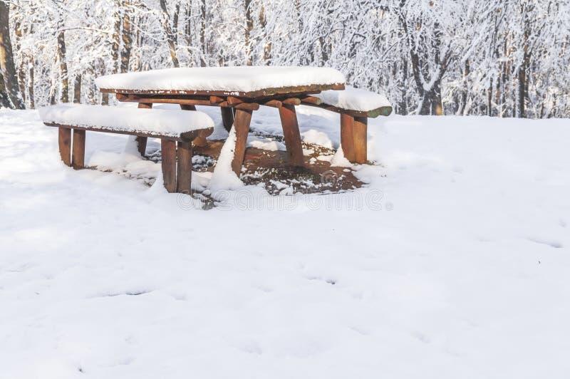 El banco de madera y la tabla cubiertos con nieve en la ciudad sazonan invierno imagen de archivo libre de regalías