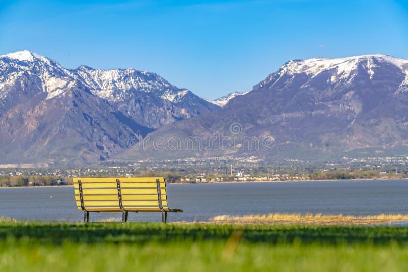 El banco vacío que hacía frente a una vista asombrosa de un lago y de una montaña capsuló con nieve fotografía de archivo