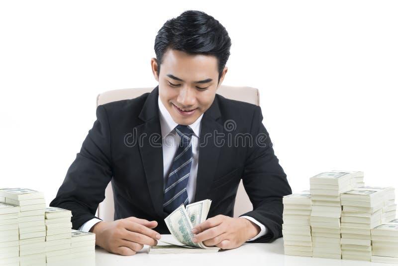El banquero masculino joven está contando billetes de banco en el fondo blanco fotos de archivo libres de regalías