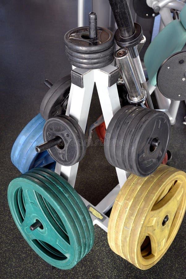 El Barbell con diversos tamaños y los pesos para el peso levantan el entrenamiento en gimnasio moderno imagenes de archivo