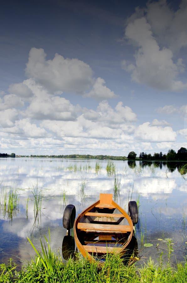 El barco amarró la reflexión de la nube de los neumáticos de goma en el agua imagen de archivo
