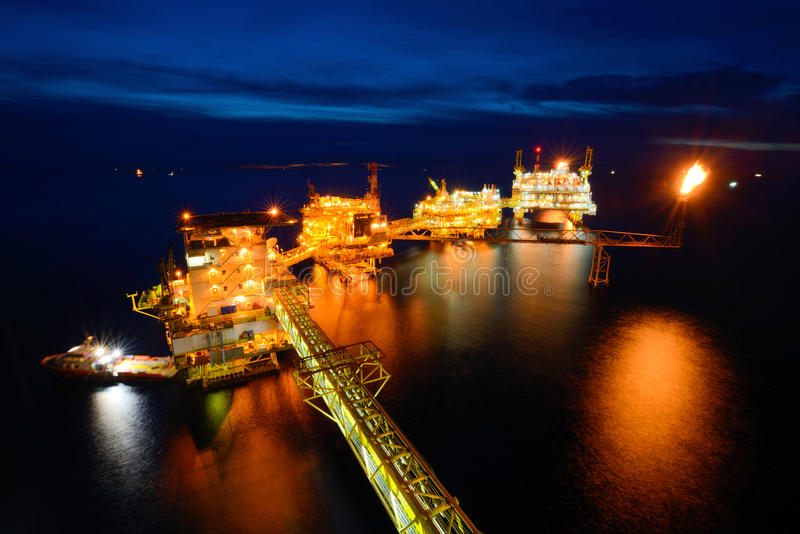 El barco de la fuente está funcionando en la plataforma petrolera costera grande en la noche fotografía de archivo libre de regalías