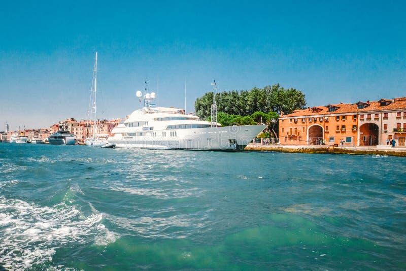 El barco de motor de alta velocidad blanco amarró a lo largo de la costa en uno de los canales en Venecia, Italia imágenes de archivo libres de regalías