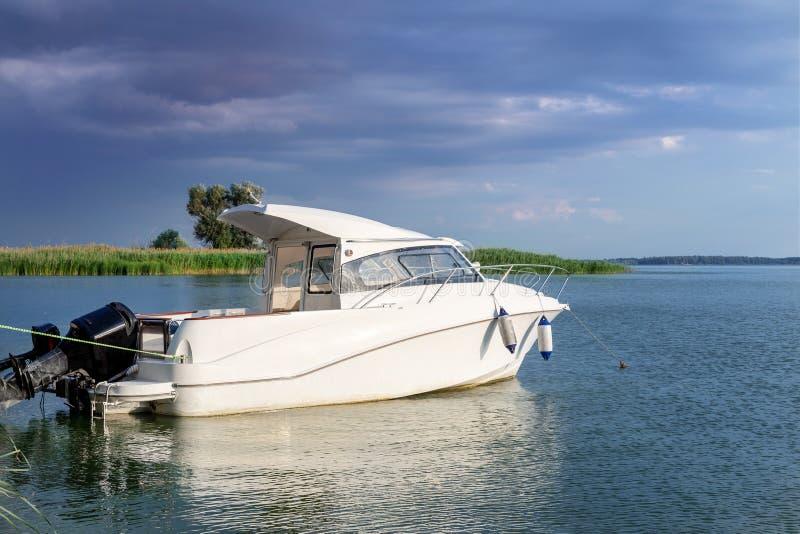El barco de motor de lujo de la pesca amarró en la costa en bahía en el río o el lago Cielo tempestuoso oscuro con las nubes de t imagen de archivo