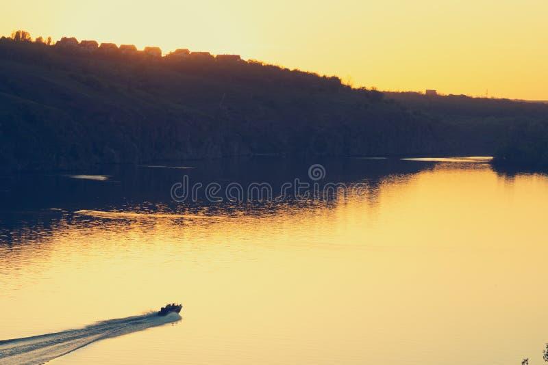 El barco de motor navega a lo largo de un río grande con las orillas rocosas fotos de archivo