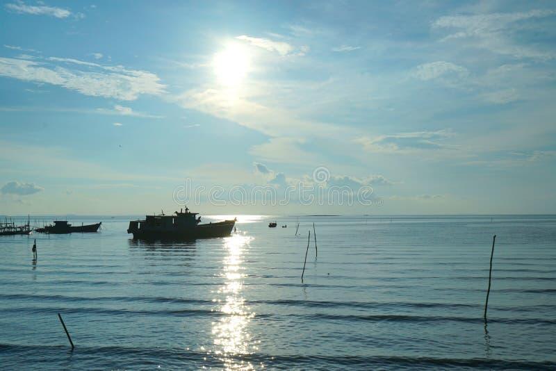 El barco de pesca de la puesta del sol de la silueta en los itse prepara a la pesca imagenes de archivo