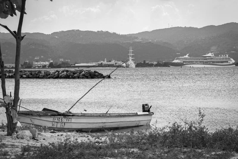 El barco de pesca por la playa en Montego Bay, y el barco de cruceros de Marella Discovery 2 atracaron en fondo fotografía de archivo