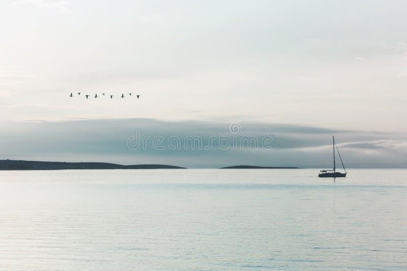 El barco de vela navega reservado en el océano iluminado por una luz surrealista fotografía de archivo