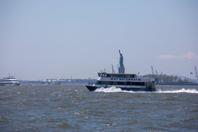 El barco del canal de NY en el Lower Manhattan con la estatua de la libertad foto de archivo libre de regalías